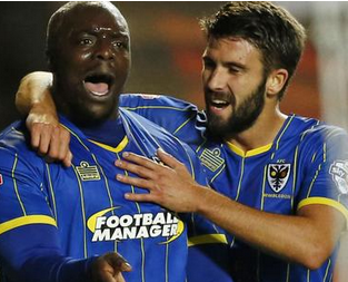 Adebayo Akinfenwa celebrates MK winner with George Francomb